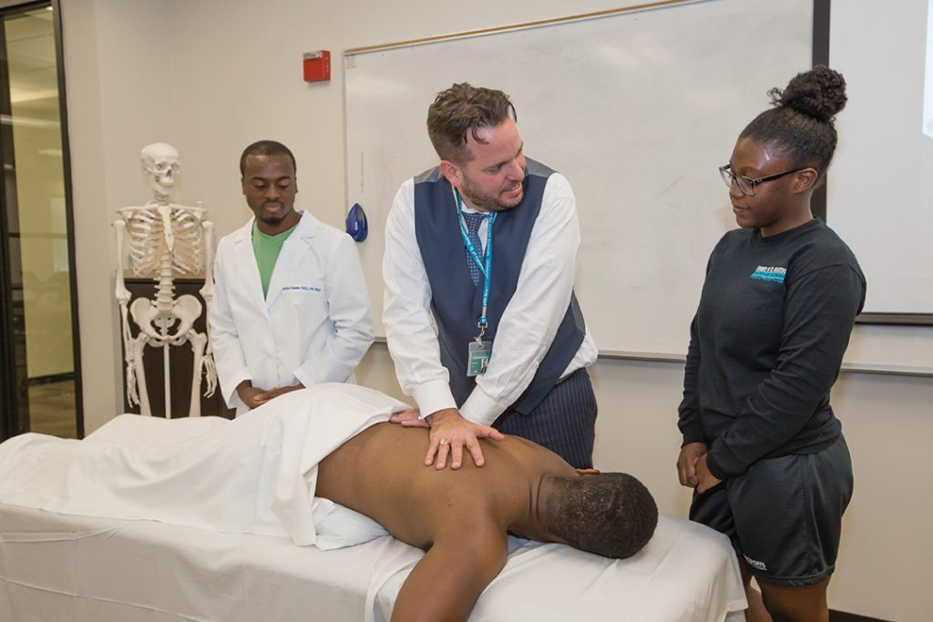 Faculty member Tomas Eberle shows students Babatunde Williams and Stacy-Ann Robinson how to mobilize the spine.