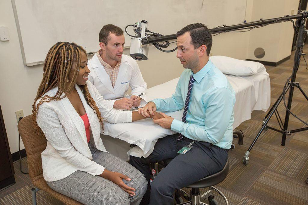 Campus Director Gabe Somarriba (right) works with students Fatmata Bangura and Donald Zerio on palpation of the hand.