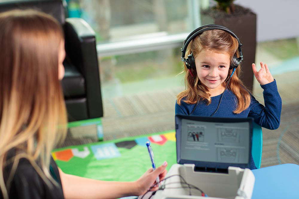 little girl with headphones on raising her left hand.