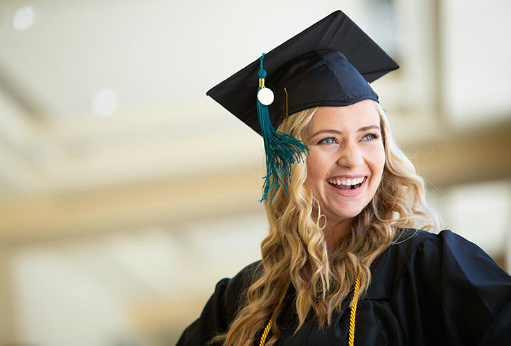 young girl smiling with cap and gown on.