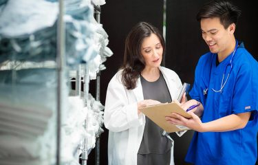 two medical professionals looking at a clipboard