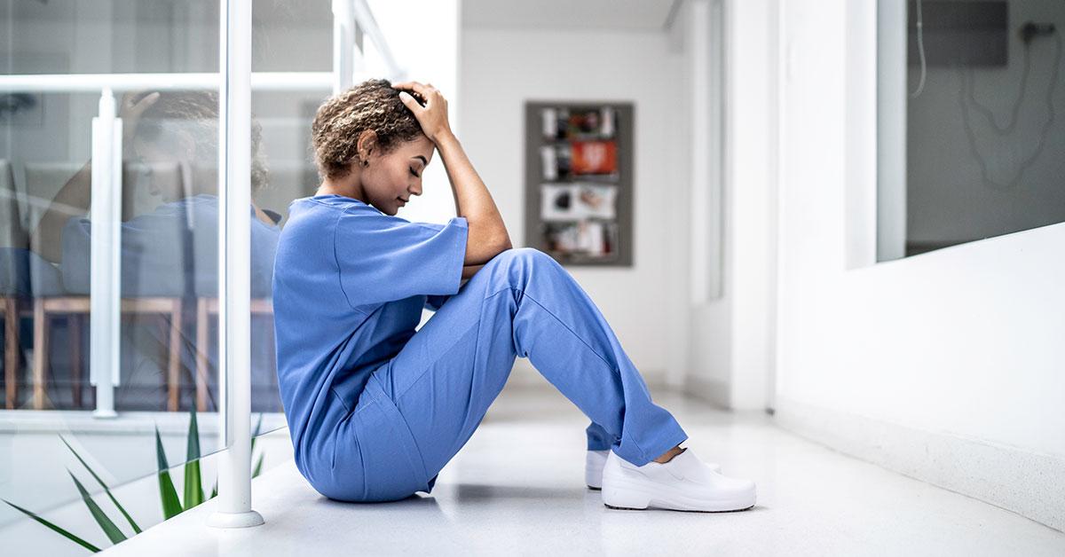 nurse sitting on floor with head in her hands