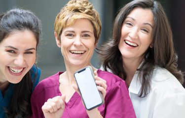 Health care workers holding a phone