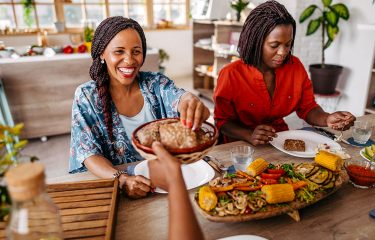 two women enjoying a plant-based meal of corn and vegetables