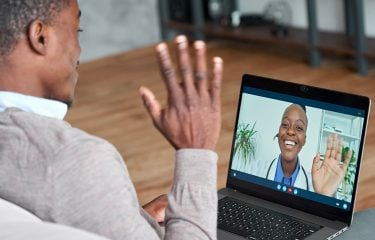 A patient is waving to his doctor over a webcam on his laptop.