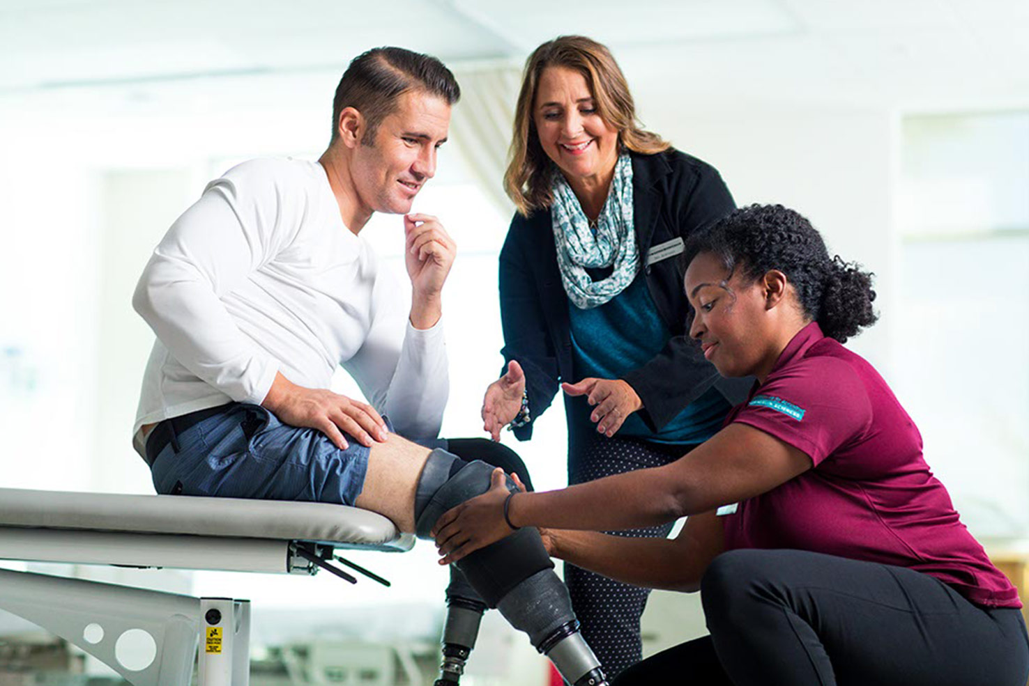 occupational therapist learning how to put a prosthetic leg on a patient