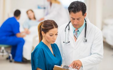 Female in blue scrubs looks at clipboard with male doctor standing next to her
