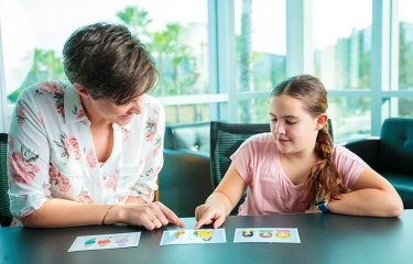 Female speech therapist seated with young girl at table pointing at flashcards