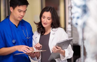 Woman in lab coat looking at clipboard held by man in blue scrub top