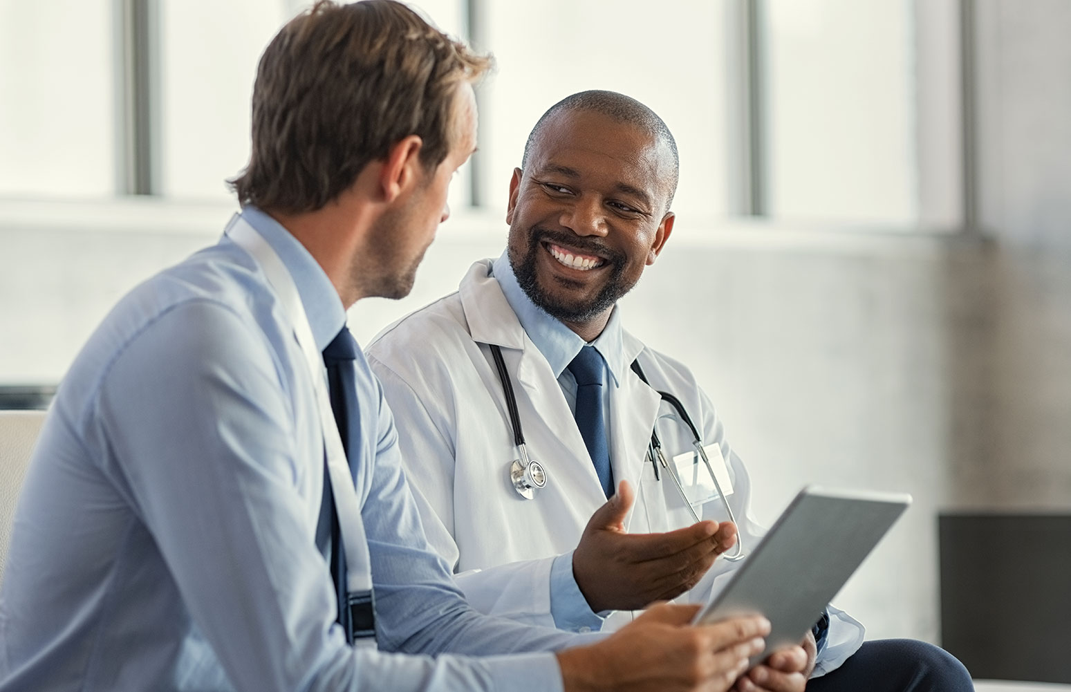 African American male doctor speaking to caucasian man in blue shirt