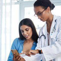 Female nurse showing female patient something on phone
