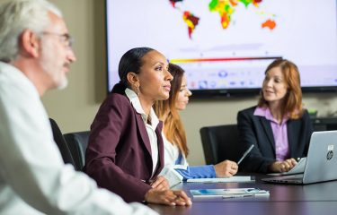 Woman in suit at conference table with 3 others