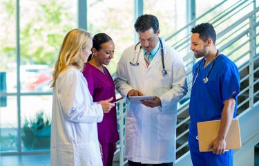 Four medical professionals discussing a chart