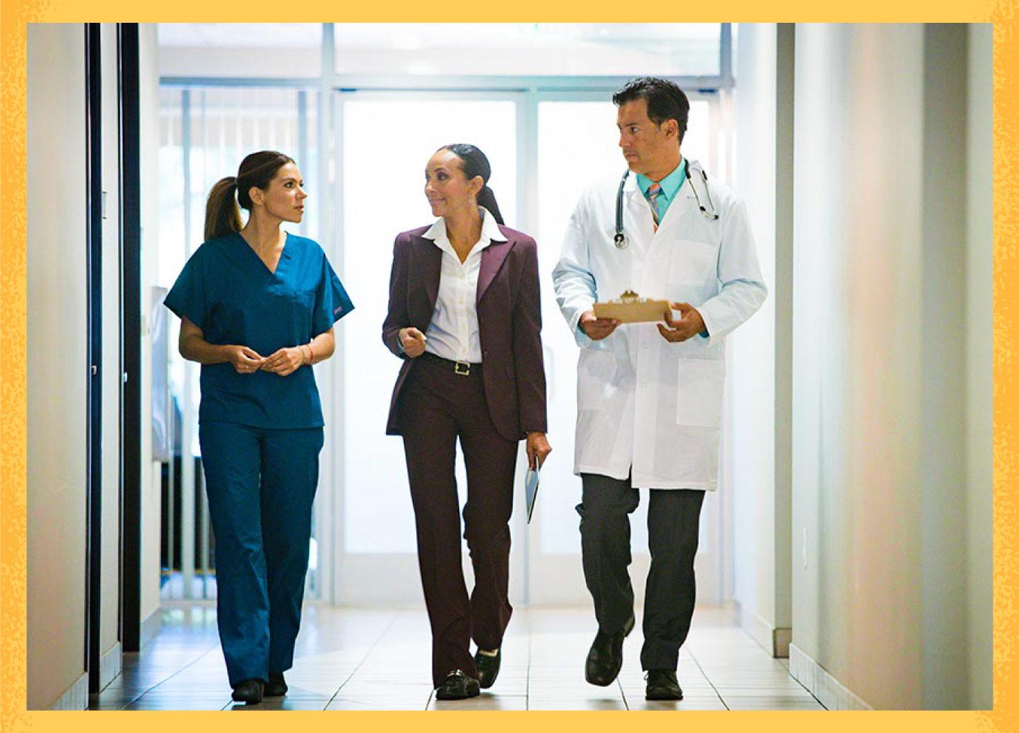 Three medical professionals walking down hallway talking